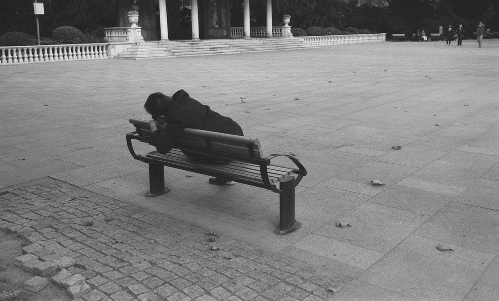 man sitting on bench in grayscale photography