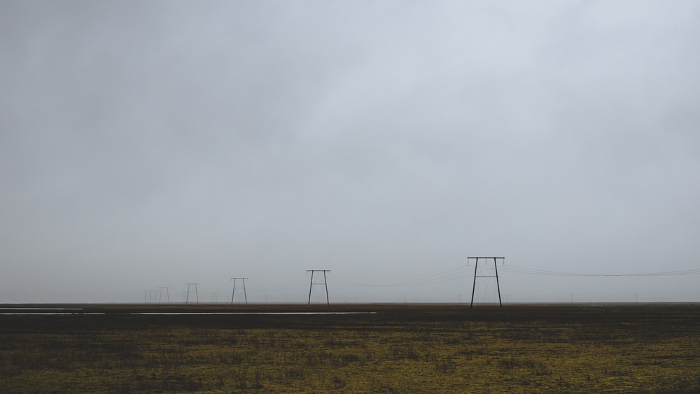 wind turbines on brown field under white sky during daytime