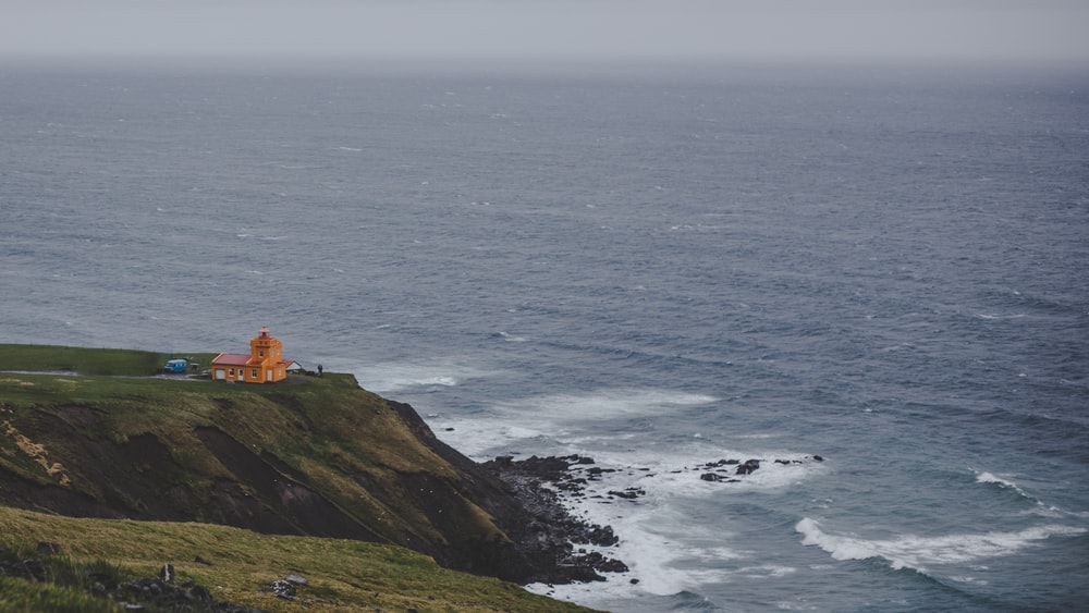 white and brown lighthouse on green mountain beside sea during daytime