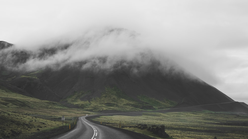 gray asphalt road near green grass field and mountain