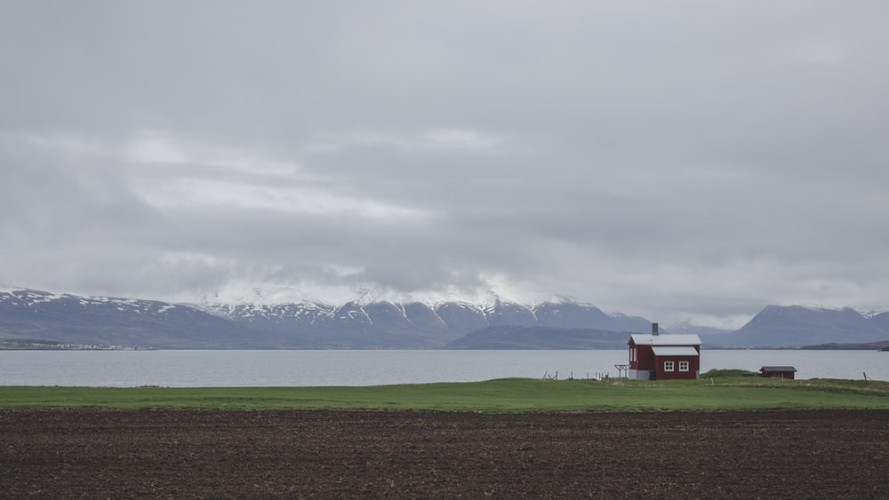 red house on green grass field near body of water under white clouds during daytime
