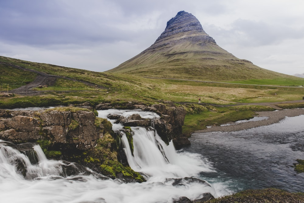 waterfalls near green grass field and mountain under white clouds during daytime