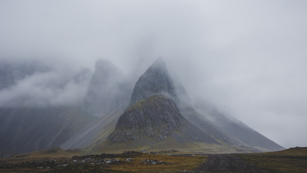 brown mountain covered by white clouds