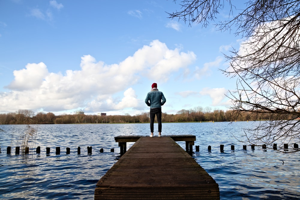 man in gray hoodie standing on wooden dock during daytime