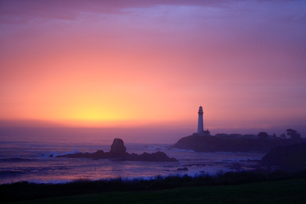silhouette of lighthouse on seashore during sunset