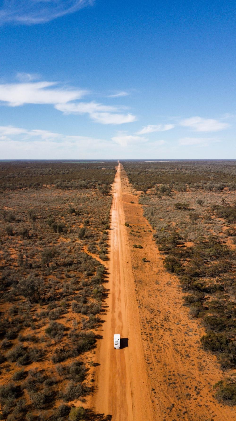 brown dirt road between green grass field under blue sky during daytime