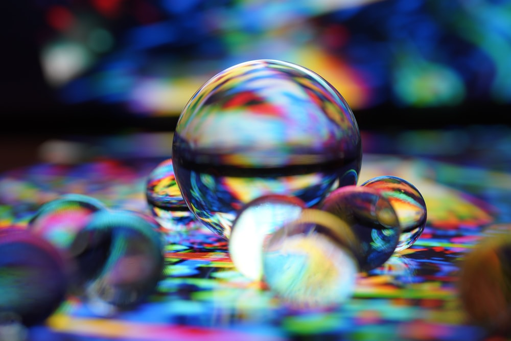 clear glass ball on blue and white textile