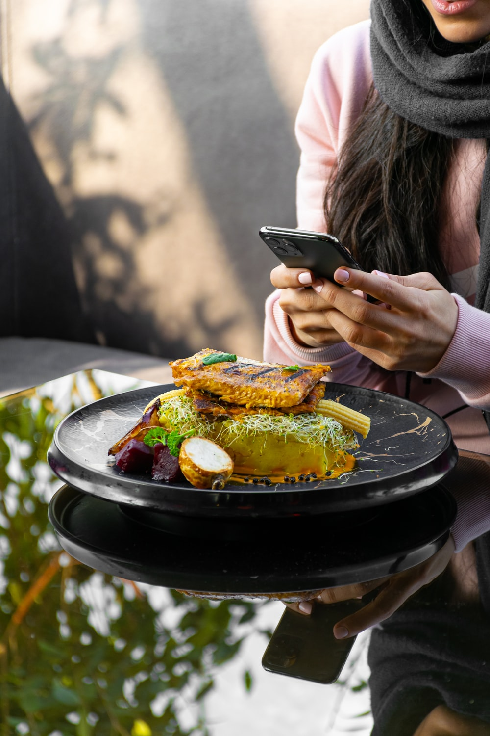 woman holding black smartphone while eating