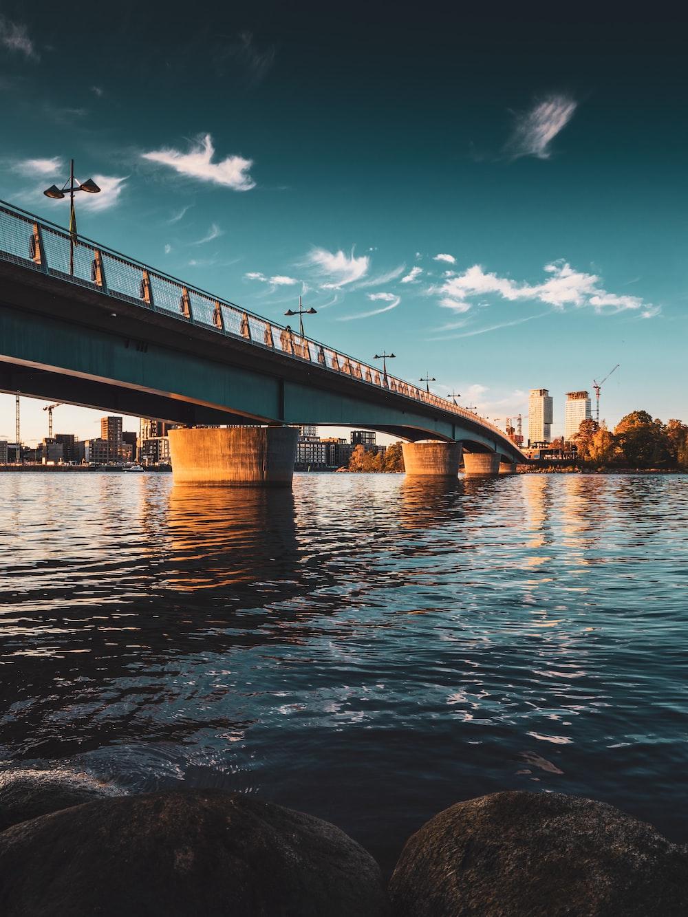 brown bridge over water under blue sky during daytime