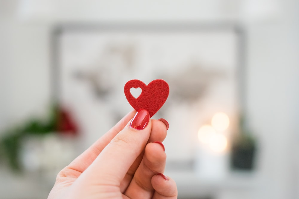 person holding pink heart ornament