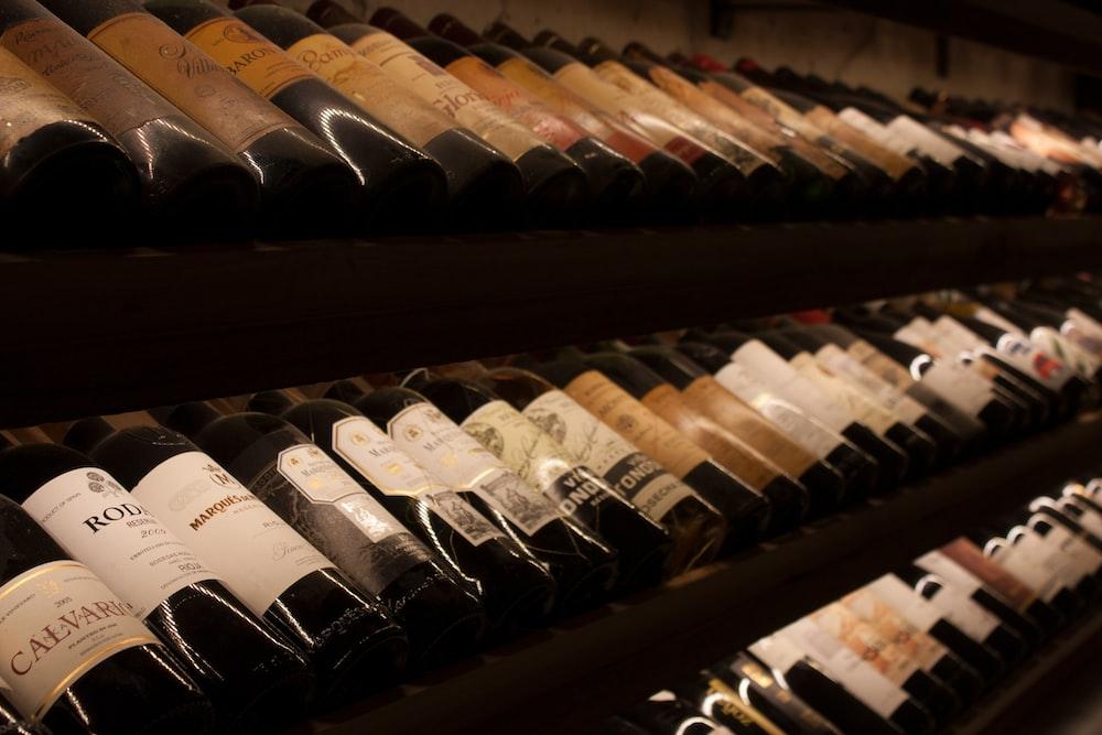 black and white bottles on brown wooden shelf