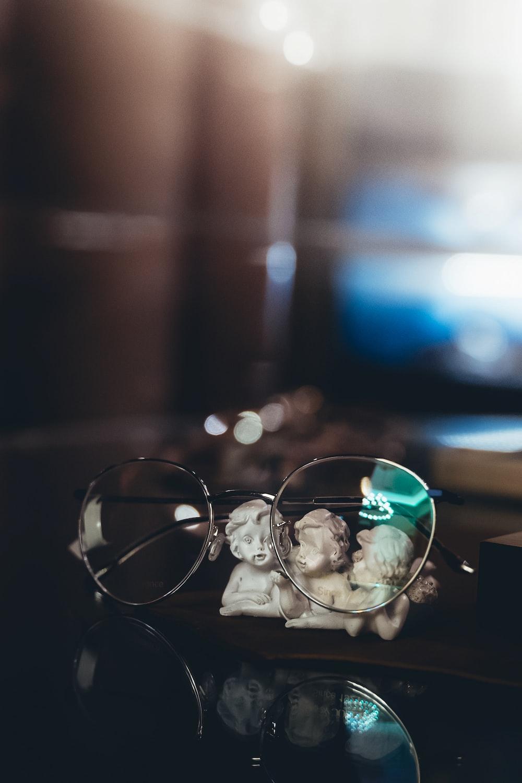 silver framed eyeglasses on brown wooden table
