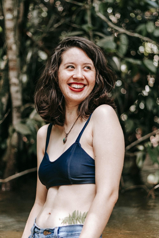 woman in blue bikini top smiling