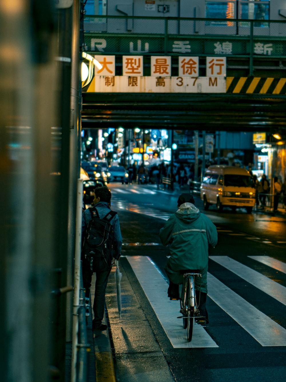 man in black jacket and black pants walking on pedestrian lane during night time
