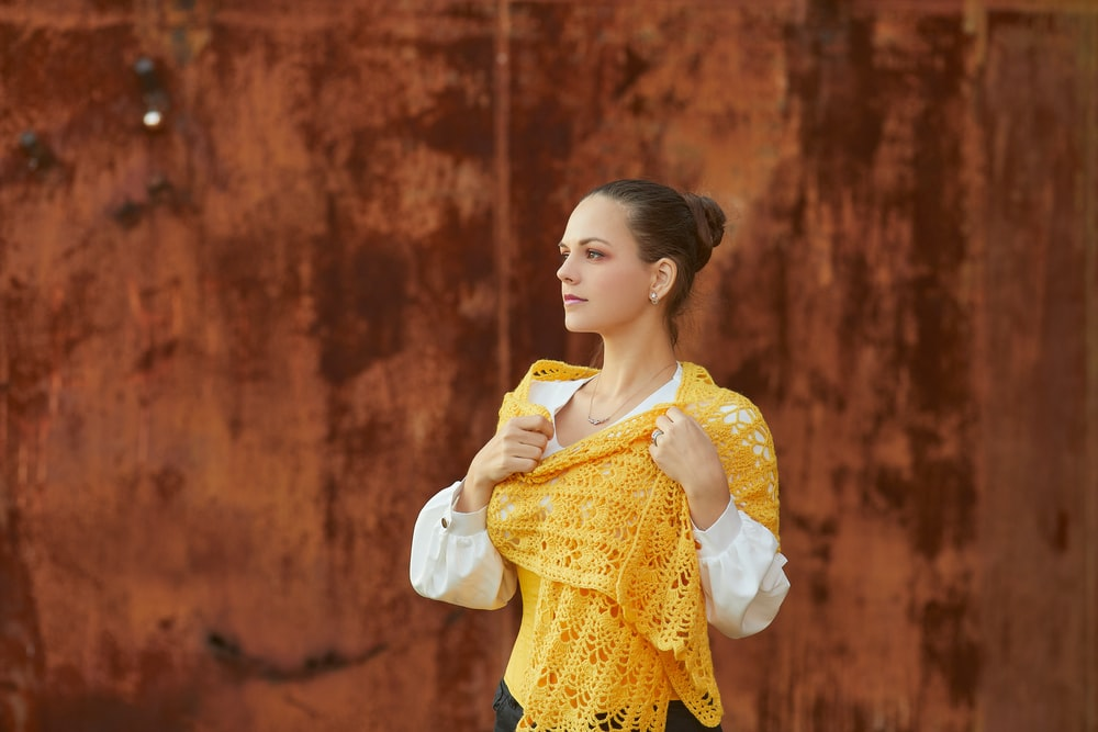 woman in yellow and white dress holding yellow scarf
