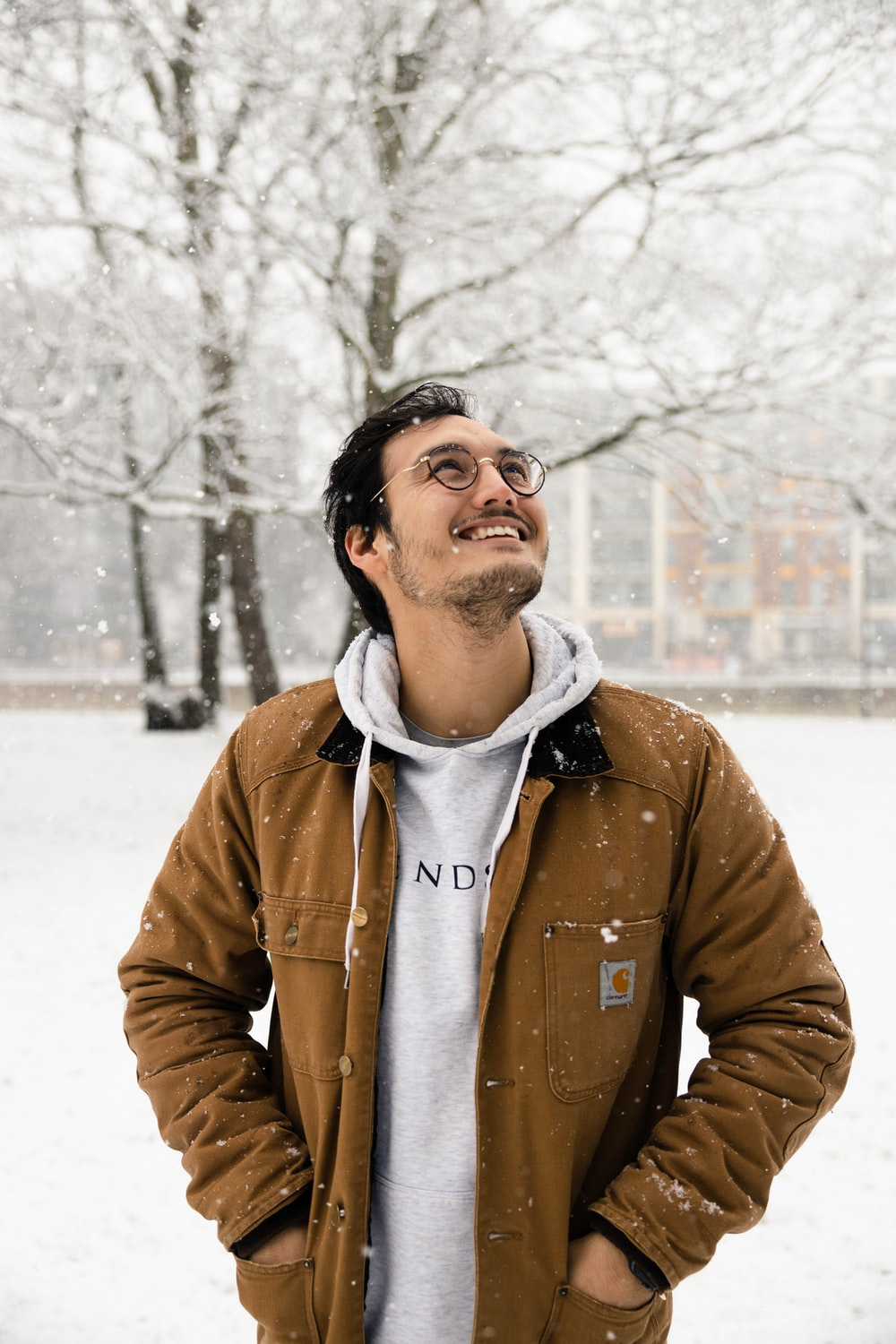 man in brown zip up jacket standing on snow covered ground during daytime