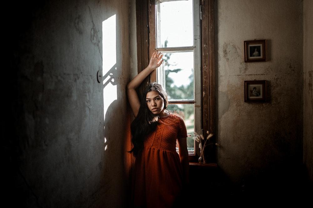 woman in orange dress standing near window