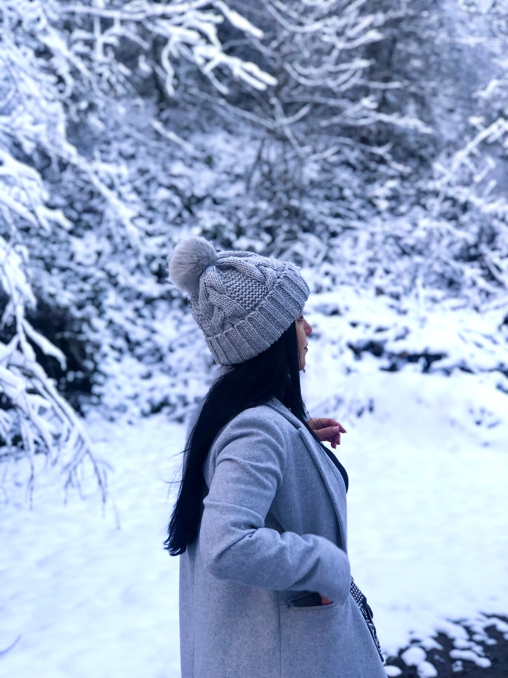 woman in gray jacket and white knit cap standing on snow covered ground during daytime