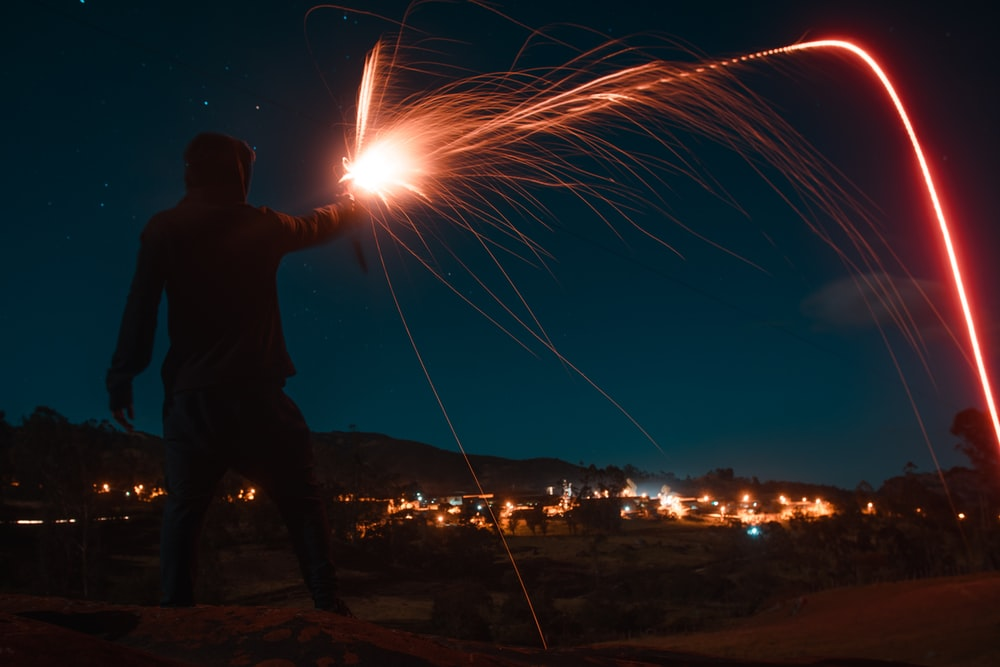 man holding fire cracker during night time