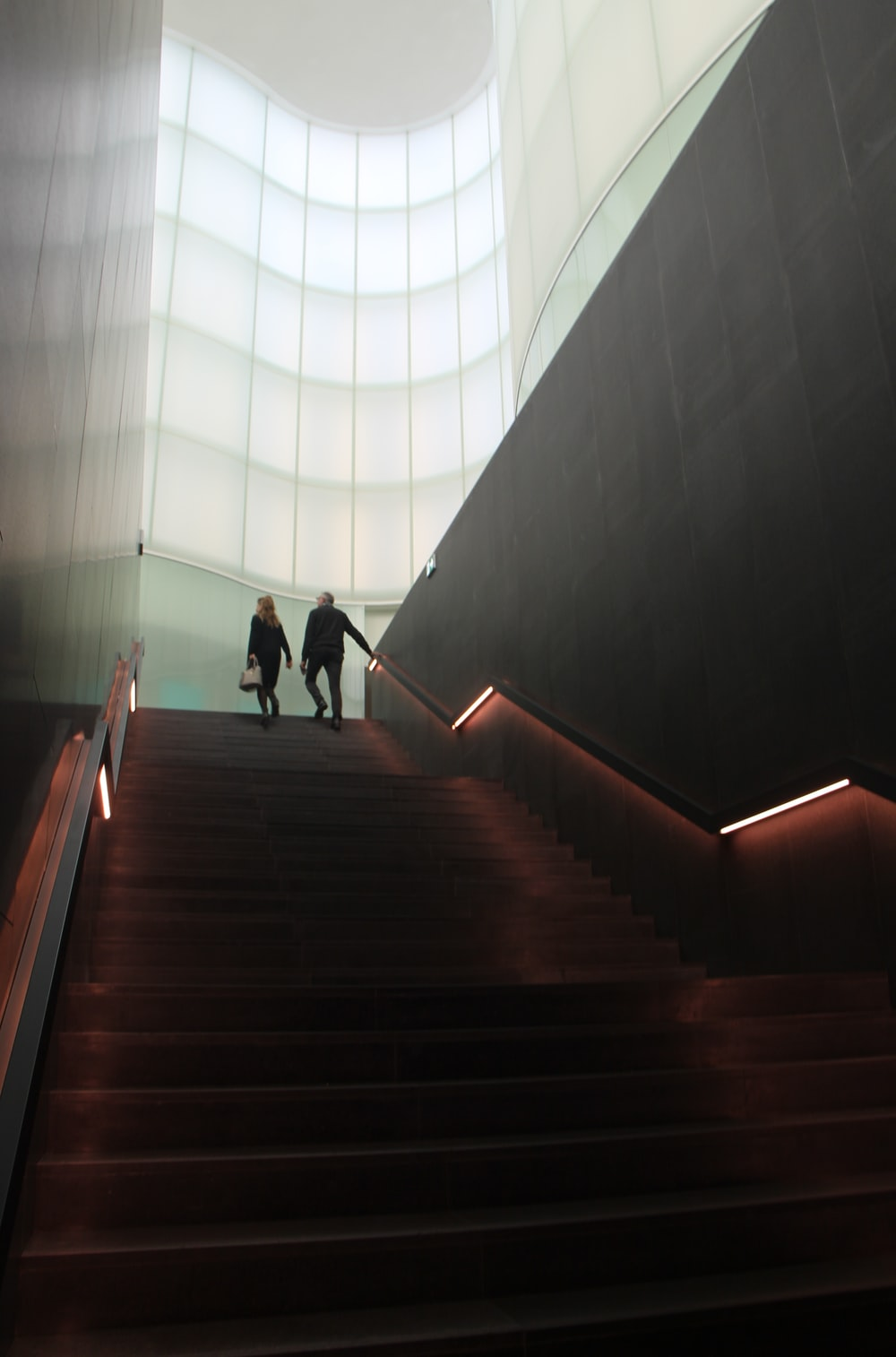 2 people walking on brown staircase