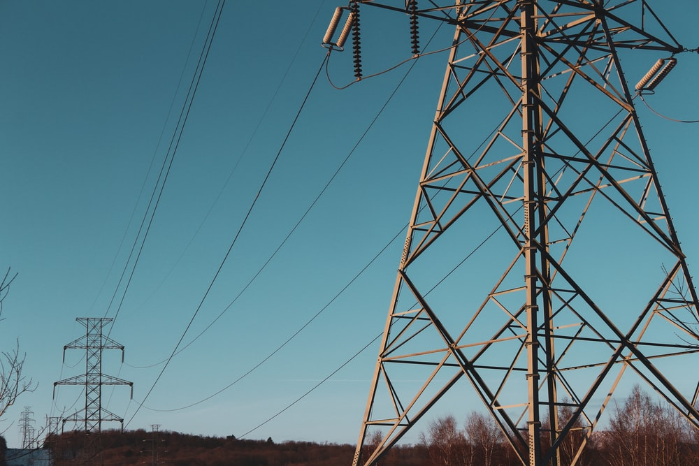 brown electric post under blue sky during daytime