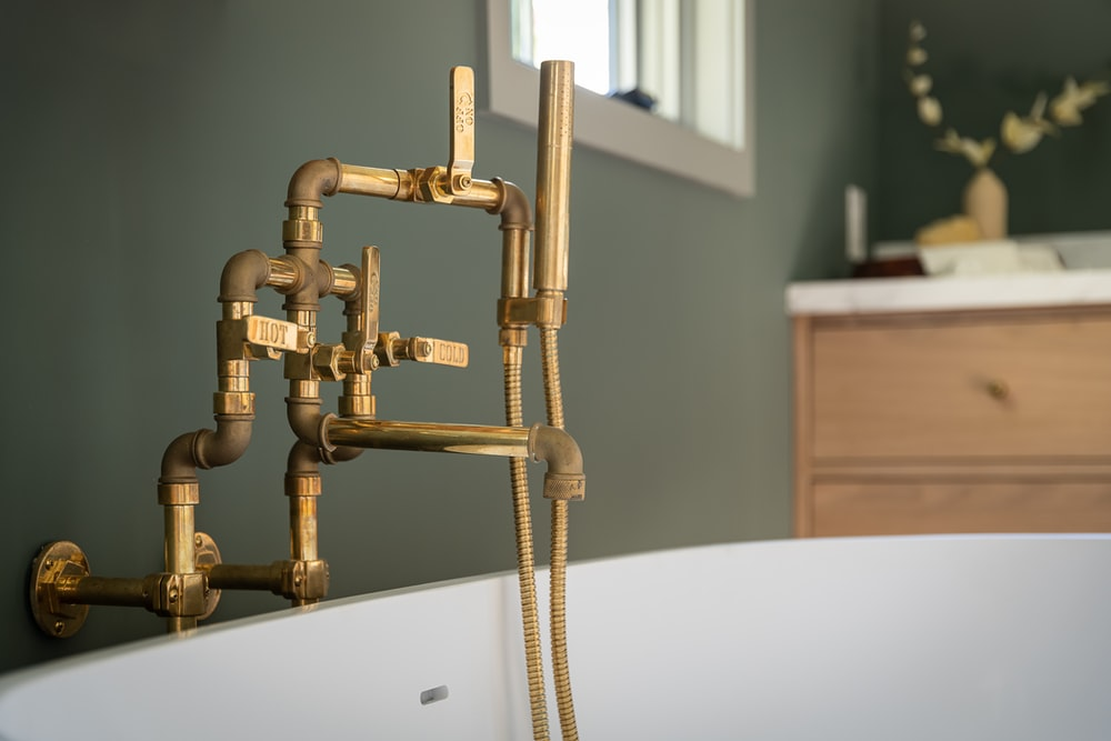 gold steel pipe on white ceramic sink