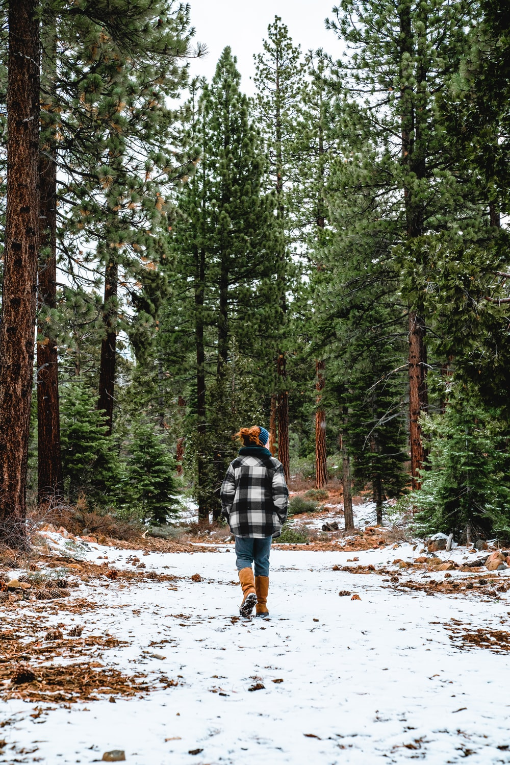 man in blue and white plaid jacket and blue denim jeans walking on snow covered pathway