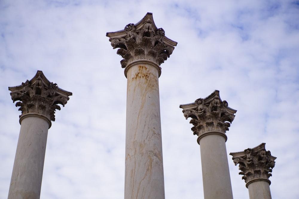 white concrete pillar under white clouds during daytime