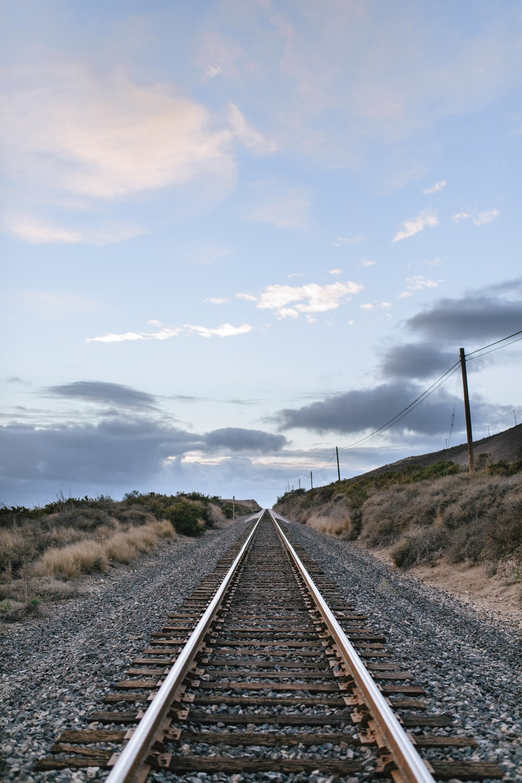 gray metal train rail under white clouds during daytime