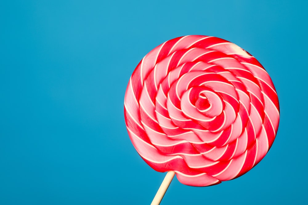white and red lollipop on blue background