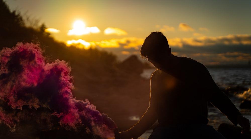 silhouette of man smoking cigarette during sunset
