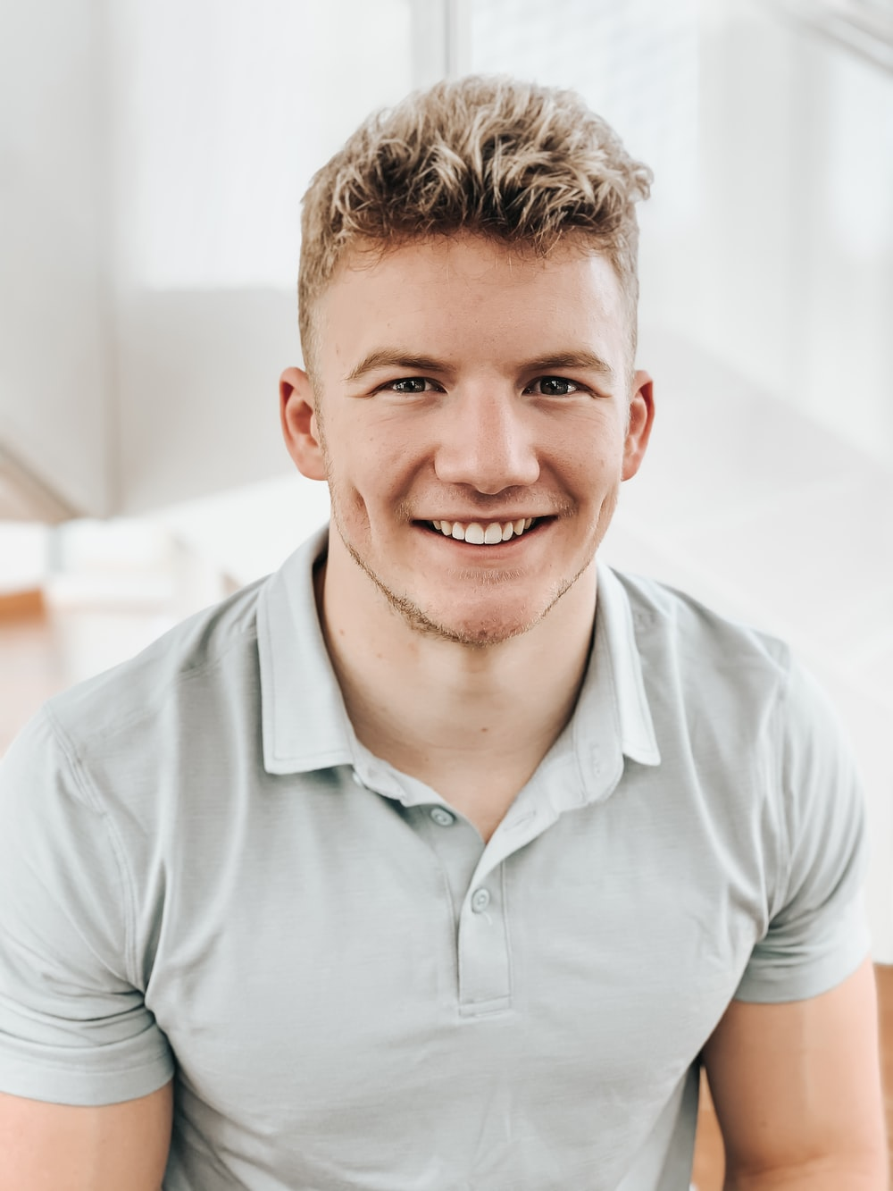 man in gray polo shirt smiling
