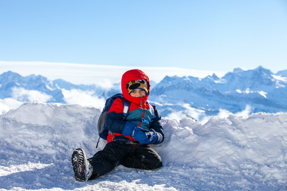 person in red and black jacket sitting on snow covered ground during daytime