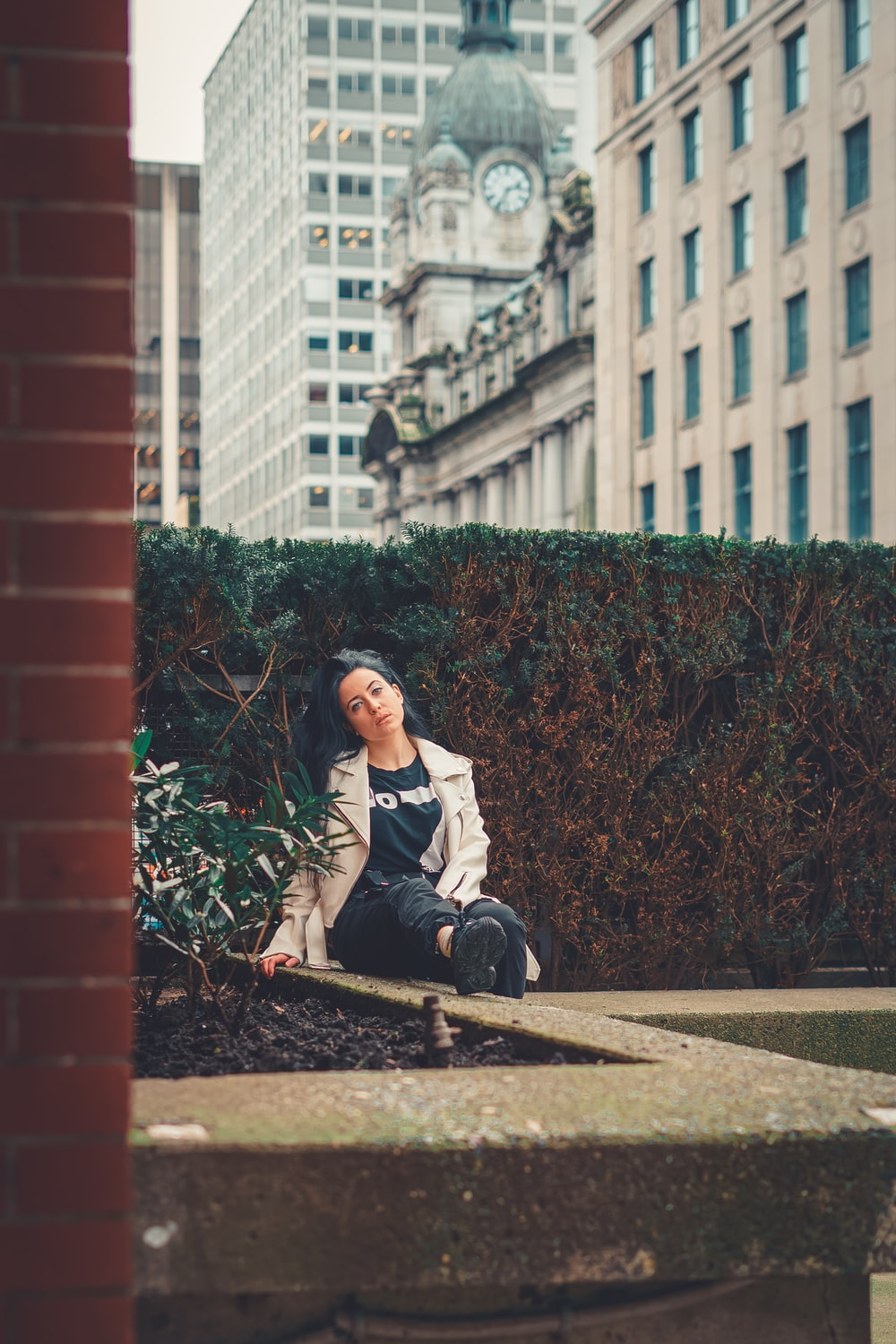 woman in white long sleeve shirt sitting on brown concrete bench during daytime