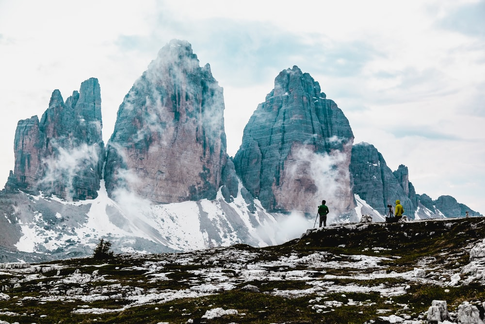 person standing on rocky mountain during daytime