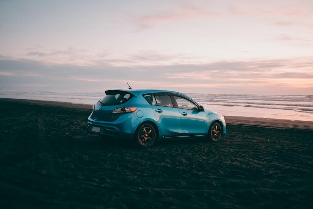 blue volkswagen beetle on beach shore during daytime