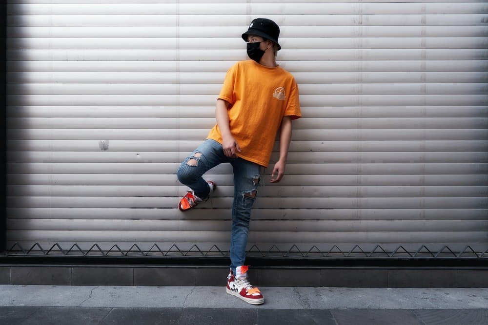 man in orange crew neck t-shirt and blue denim jeans standing on black and white
