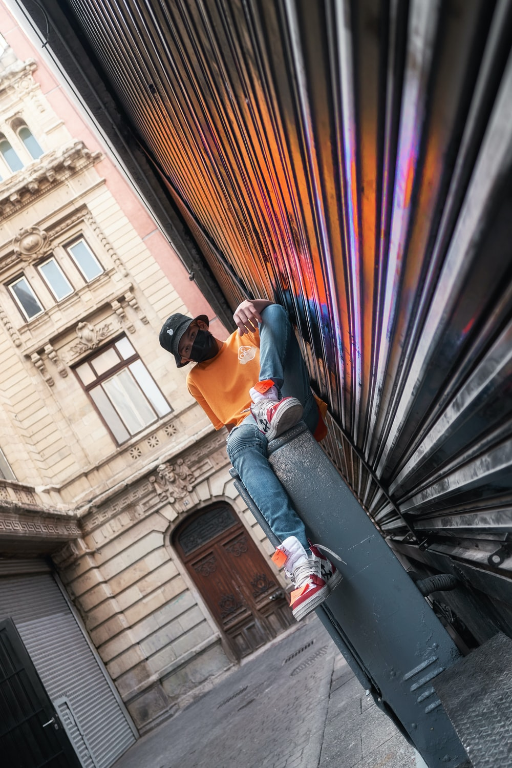 man in orange t-shirt and blue denim jeans sitting on black metal staircase