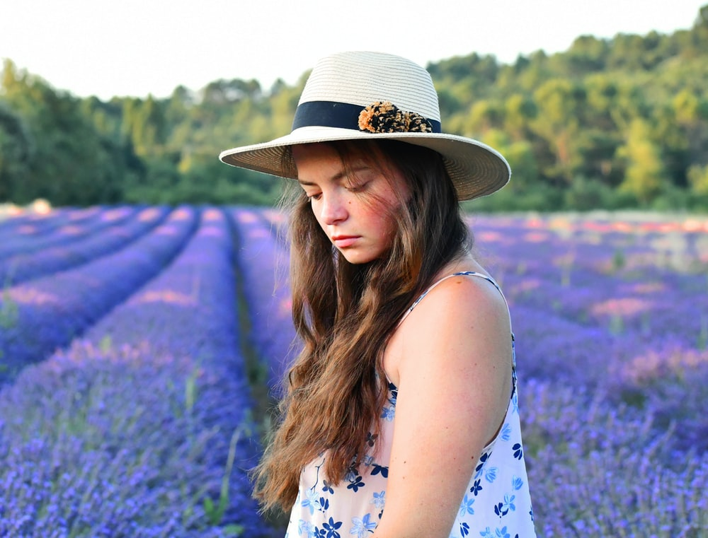 woman in blue and white floral sleeveless dress wearing brown hat standing on purple flower field
