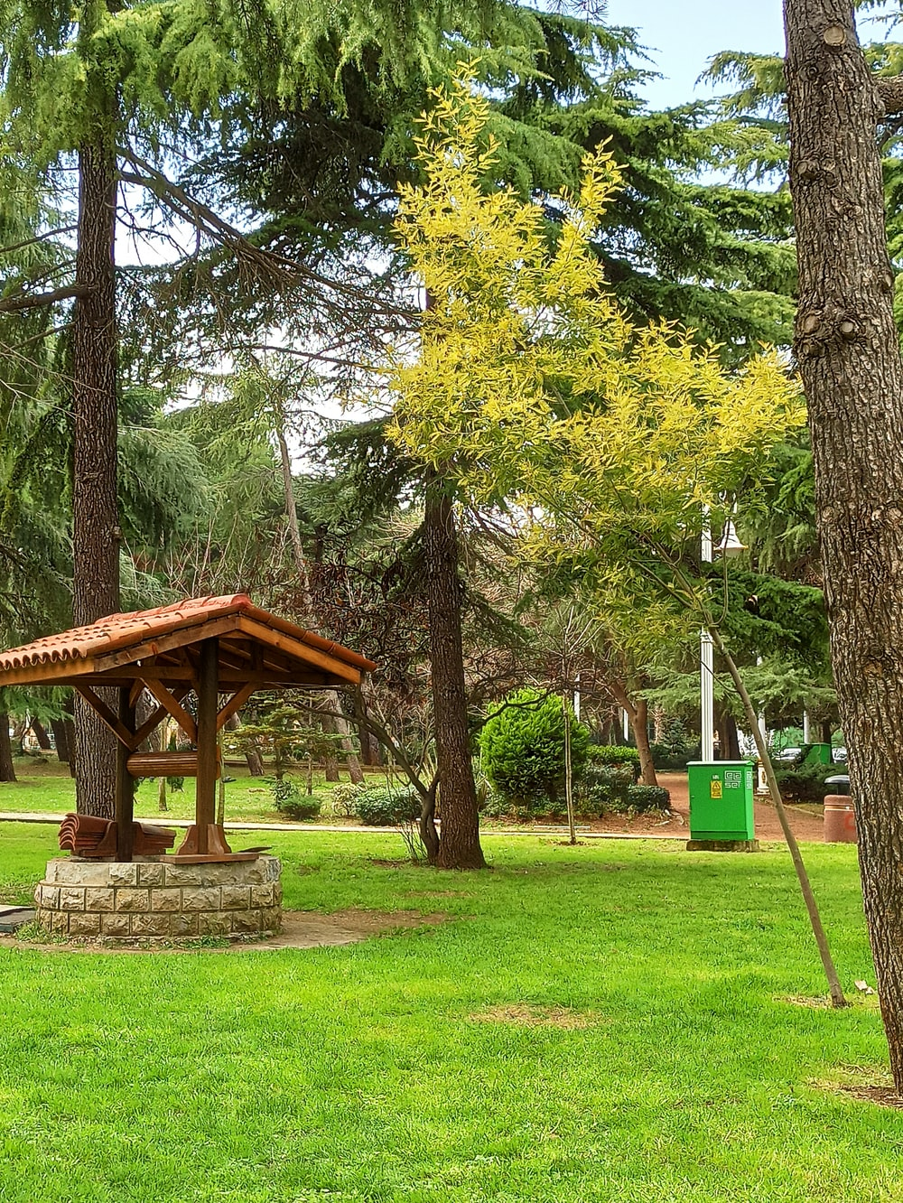 brown wooden gazebo in the middle of green grass field