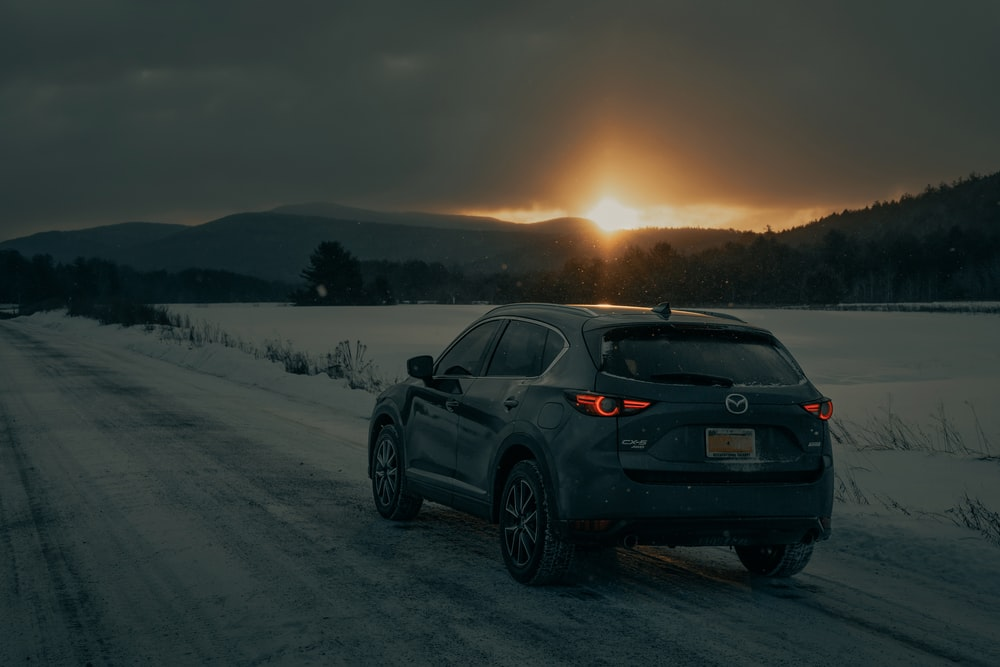 black bmw x 6 on snow covered field during daytime