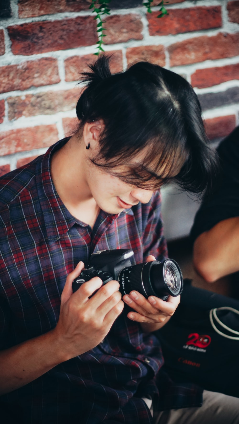 woman in black and red plaid button up shirt holding black dslr camera