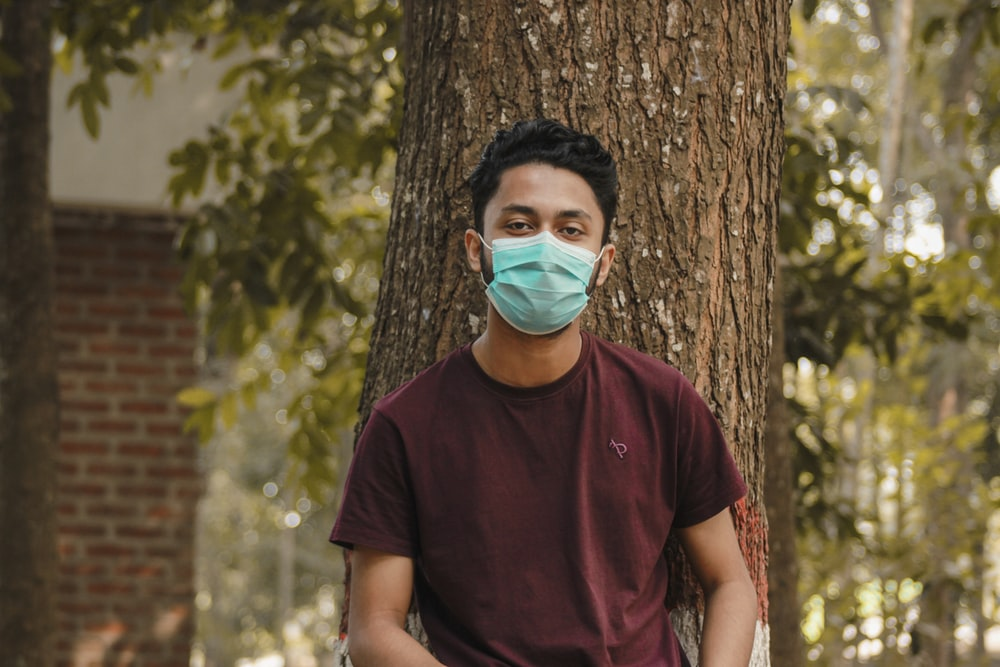 man in maroon crew neck t-shirt with face mask standing beside brown tree during daytime