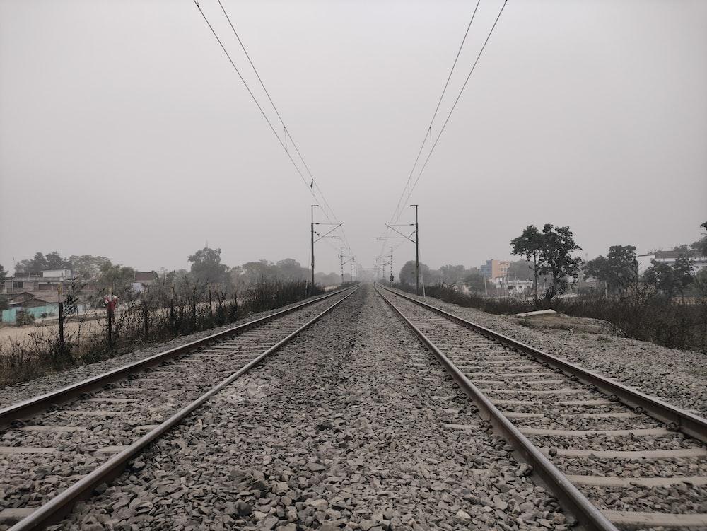 train rail tracks under white sky during daytime