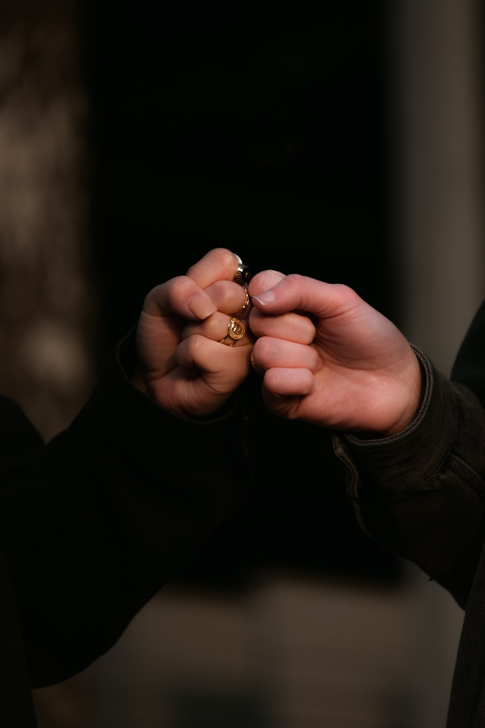 person holding gold ring in dark room