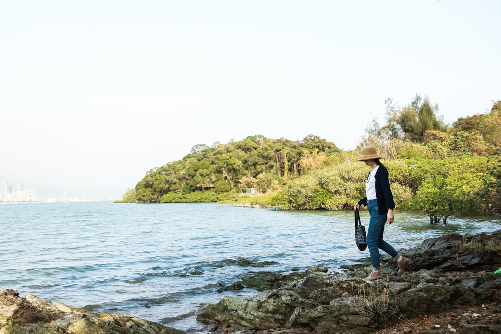woman in black shirt and blue denim jeans standing on rocky shore during daytime