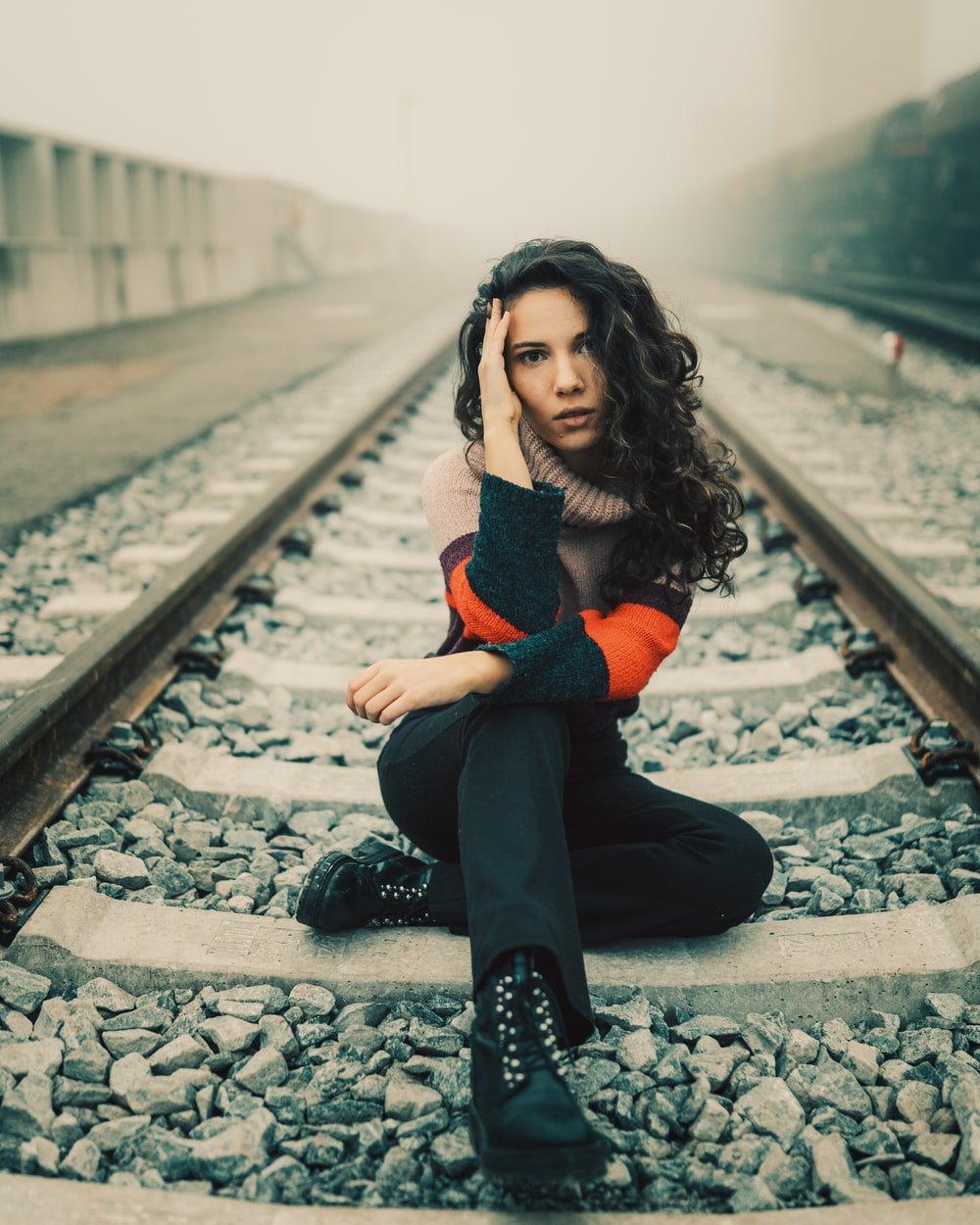 woman in black and orange long sleeve shirt sitting on train rail during daytime
