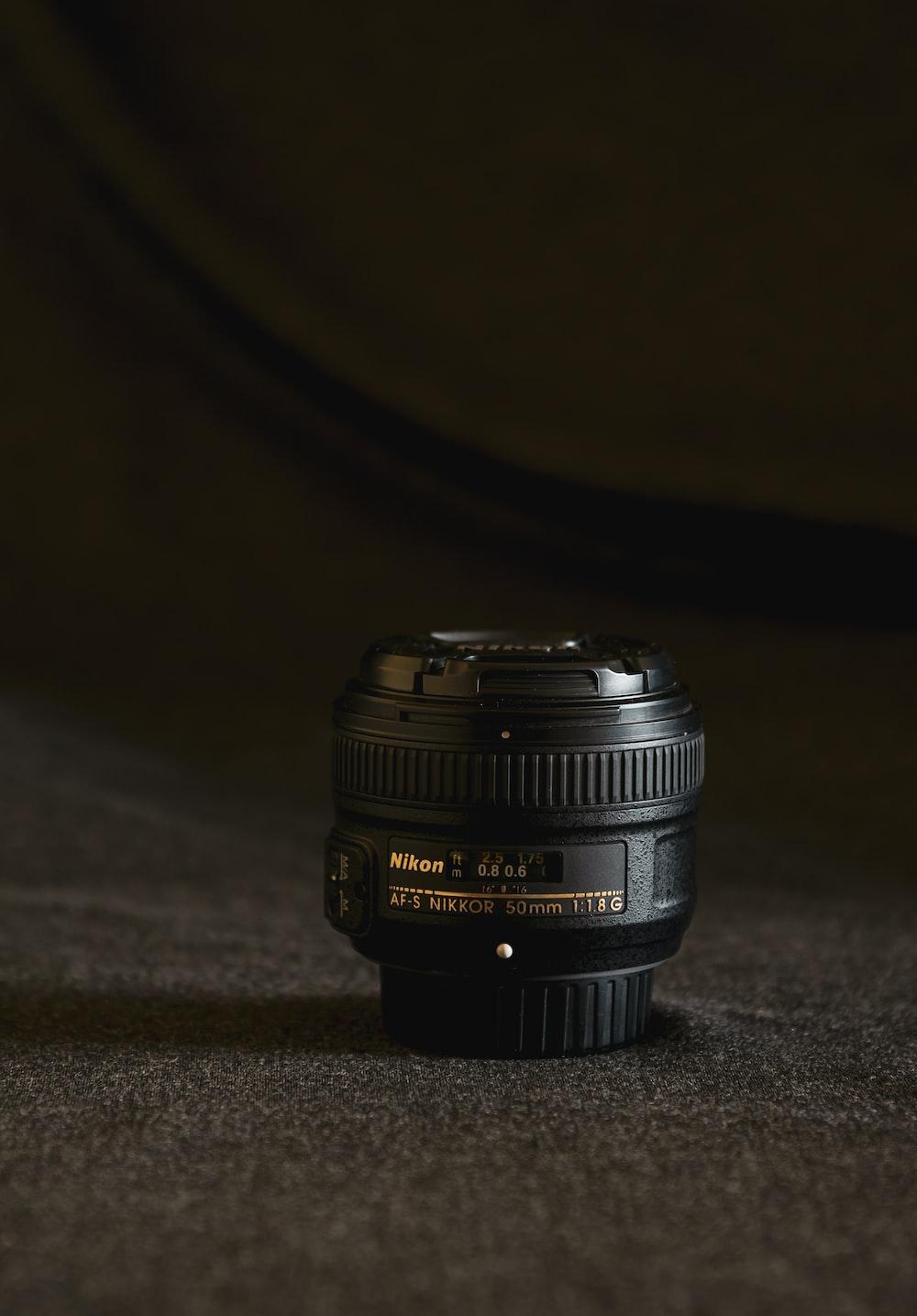 black nikon camera lens on gray textile