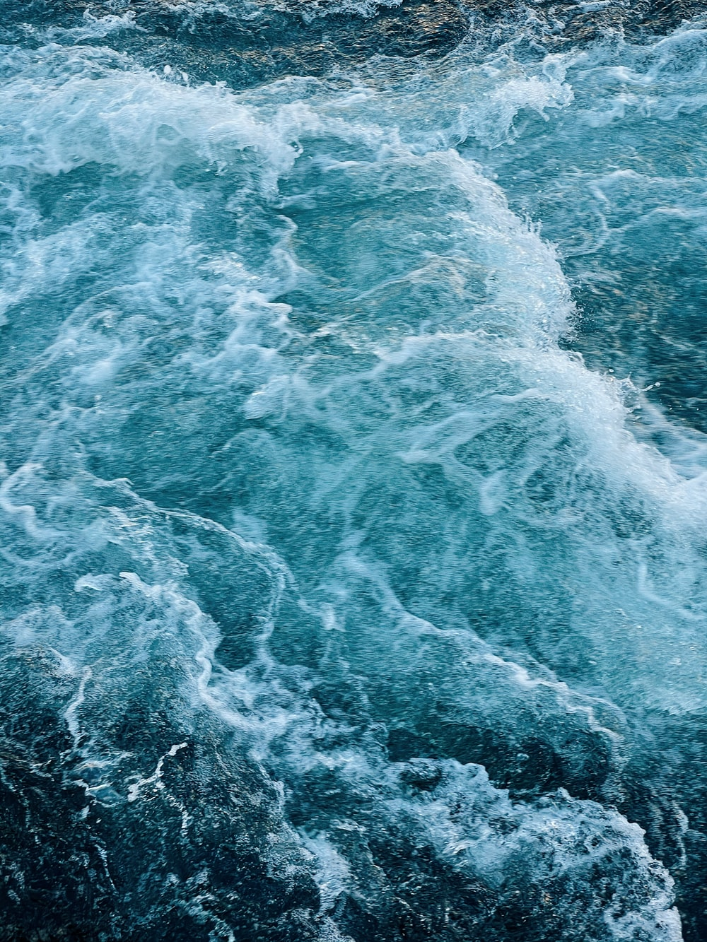 water waves on blue body of water