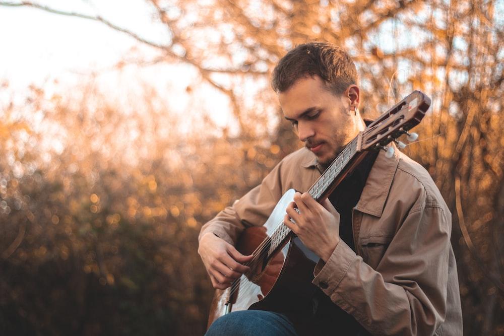 man in brown coat playing guitar